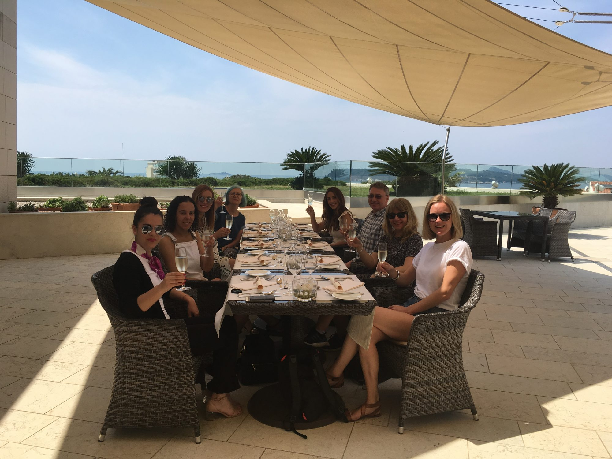 Group of people enjoy lunch on a sunny terrace shaded by a sunsail